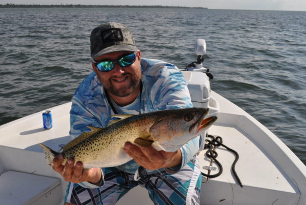 a picture of a fisherman holding a sea trout caught in tampa bay