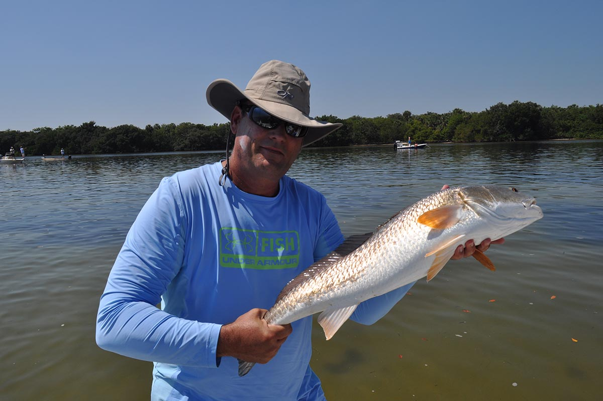fisherman holding a fresh caught redfish out of Clearwater Florida