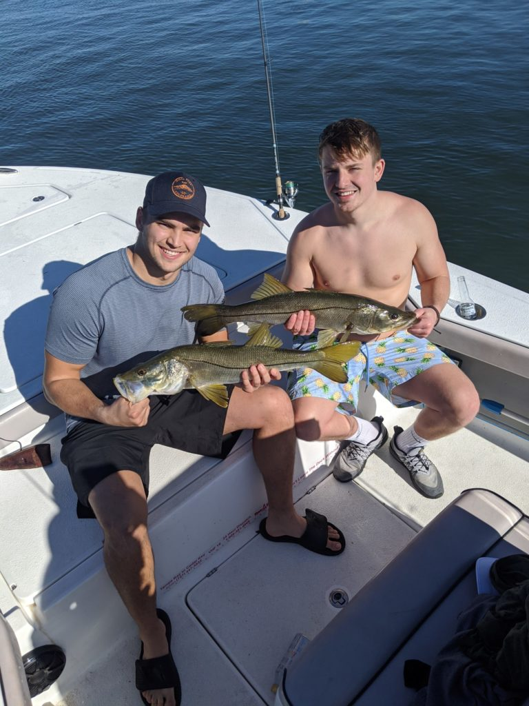 a picture of two fisherman each holding a snook they caught in tampa bay