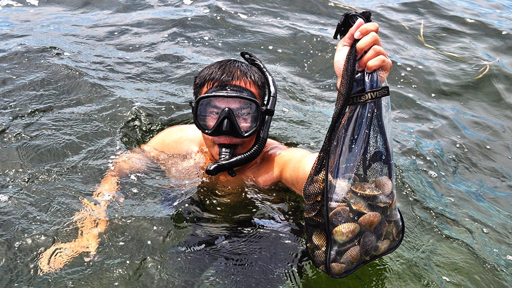 Swimmer holding a bag of Homosassa scallops